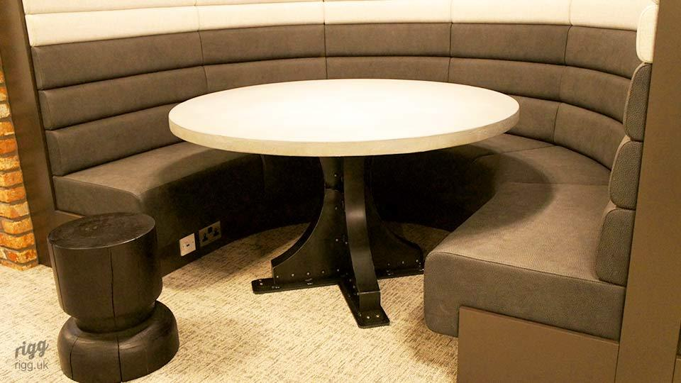 Industrial Round Concrete Table with Rivets in Booth