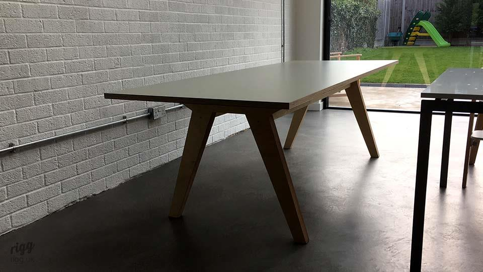 Synk Plywood Dining Table Against White Brick Wall